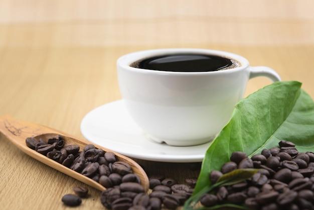 Tazza di caffè con chicchi di caffè e foglie di caffè