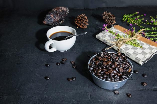 Tazza di caffè con chicchi di caffè e taccuino