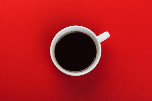 Tazza di caffè con chicchi di caffè su rosso.