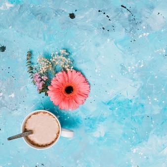 Tazza di caffè con fiori sul tavolo blu