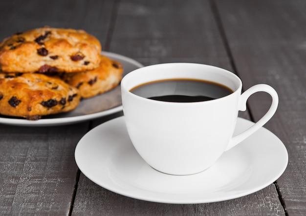 Tazza di caffè con focaccine al latte frutta fresca con uvetta sul tavolo di legno