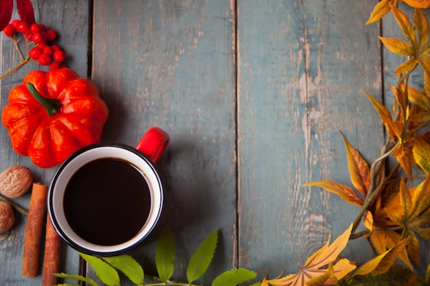 Tazza di caffè con foglie di autunno e piccole zucche