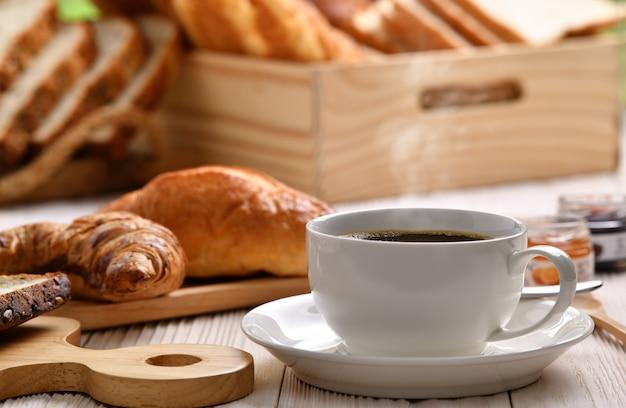 Tazza di caffè con fumo con pane o panino, cornetto e forno sulla tavola di legno bianca