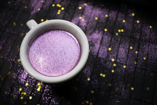 Tazza di caffè con glitter viola su sfondo scuro