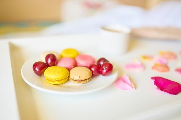 Tazza di caffè con gustosi macarons colorati o amaretti sul vassoio bianco.