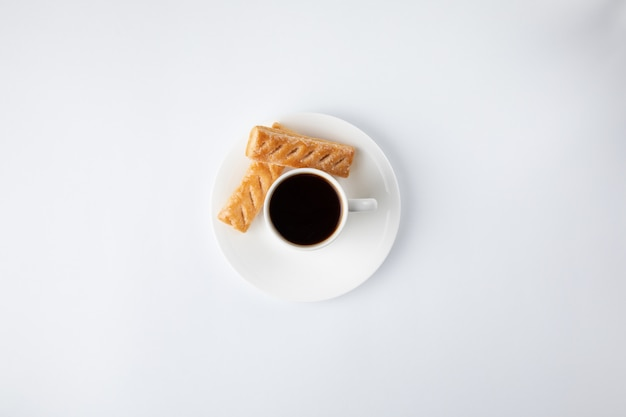 Tazza di caffè con i dolci isolati su bianco