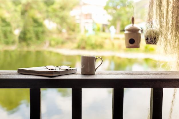Tazza di caffè con i vetri dell'occhio e del libro sulla cima di legno.