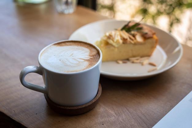 Tazza di caffè con il dolce della torta di mele con sulla tavola di legno