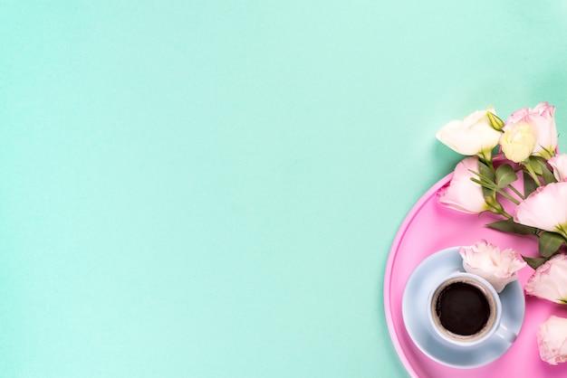 Tazza di caffè con il eustoma rosa del mazzo su un vassoio della rosa sopra fondo blu con copyspace, disposizione piana.