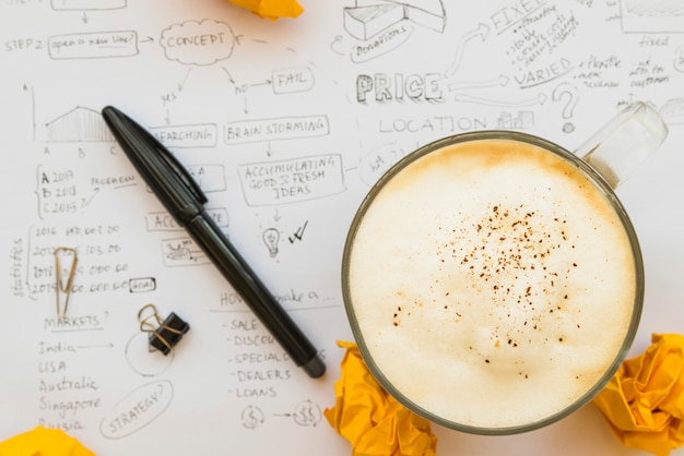 Tazza di caffè con la penna sul foglio di carta di lampo di genio