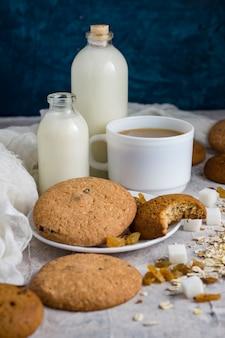 Tazza di caffè con latte in una tazza bianca, bottiglie con latte, biscotti di farina d'avena, farina d'avena, uvetta su una superficie leggera. scena da colazione