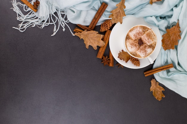 Tazza di caffè con marshmallow, cacao, sciarpa, foglie, arance secche, spezie, su sfondo grigio. deliziosa bevanda autunnale calda, umore mattutino. copyspace.