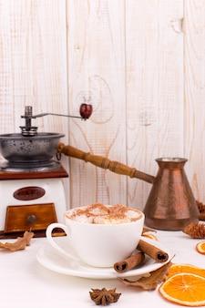 Tazza di caffè con marshmallow e cacao, foglie, arance secche, spezie, su uno sfondo bianco. deliziosa bevanda autunnale calda, umore mattutino. copyspace.