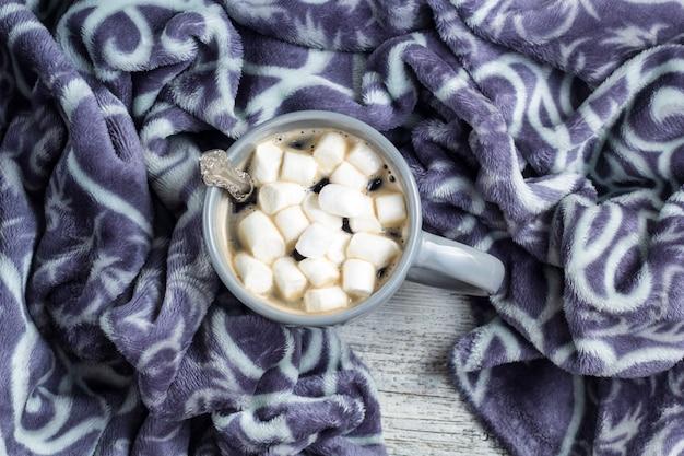 Tazza di caffè con marshmallow e caldo plaid sul tavolo di legno bianco. concetto di natale inverno.