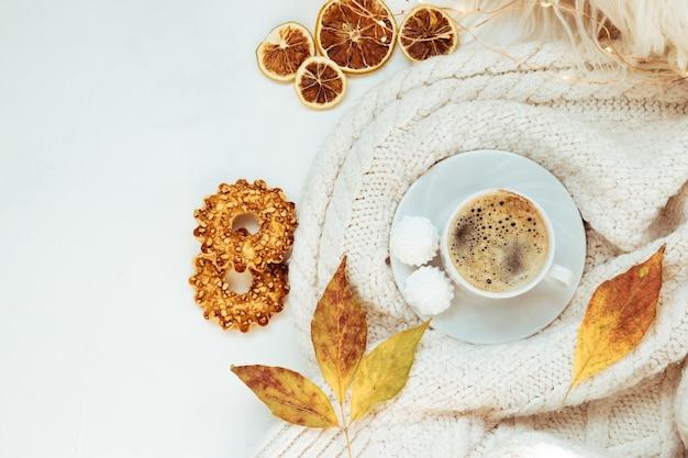 Tazza di caffè con meringhe e biscotti su un tavolo bianco - vista dall'alto. concetto di autunno
