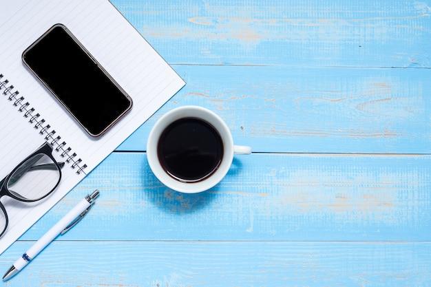 Tazza di caffè con occhiali penna, notebook e occhi