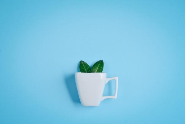 Tazza di caffè con orecchie di coniglio bunny fatto di foglie verdi naturali su sfondo blu.