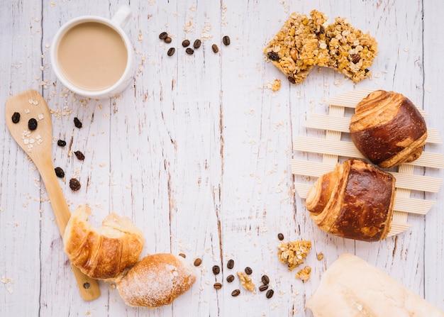 Tazza di caffè con panetteria diversa sul tavolo di legno