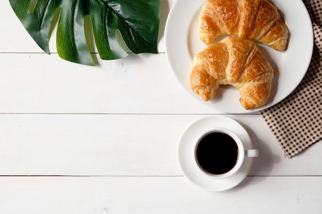 Tazza di caffè con piatto bianco e cornetti sul tavolo di legno bianco.