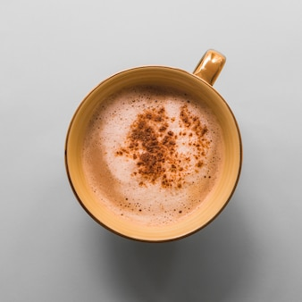 Tazza di caffè con schiuma di latte e cacao in polvere su sfondo grigio