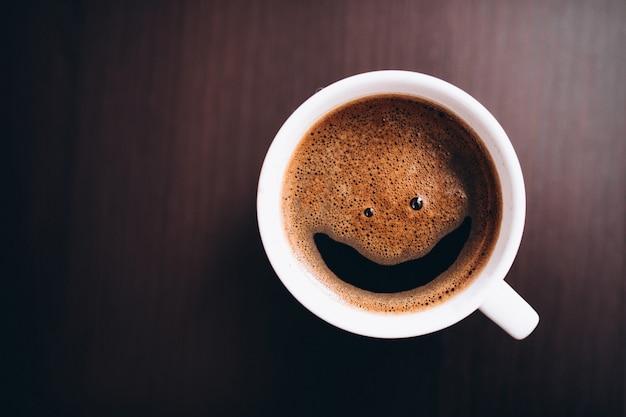 Tazza di caffè con schiuma, sorriso viso, sulla scrivania isolata
