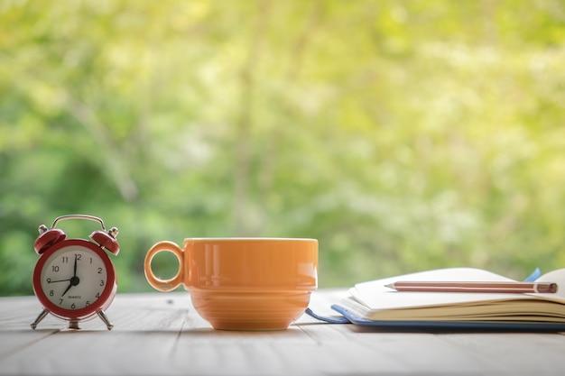 Tazza di caffè con taccuino, penna e sveglia su un tavolo da tavola di legno in sfondo naturale.