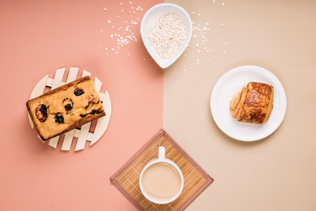 Tazza di caffè con torta e panino sul tavolo