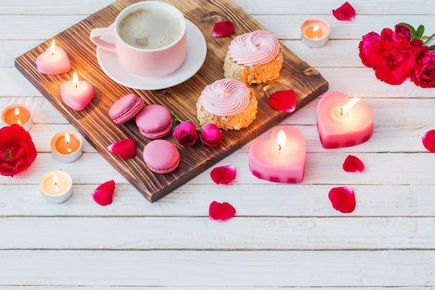 Tazza di caffè con torte, candele e rose sul retro in legno bianco