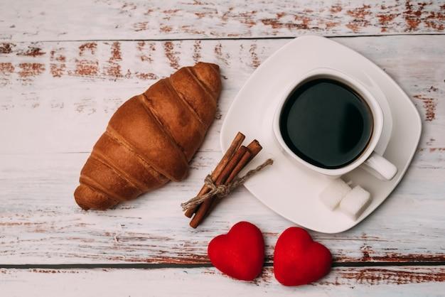 Tazza di caffè con un cornetto e cuori sul tavolo di legno. concetto di mattina colazione a san valentino