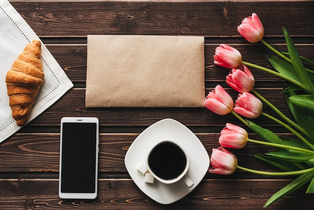 Tazza di caffè con un cornetto per la colazione sul tavolo decorato con un mazzo di tulipani rosa e uno smartphone
