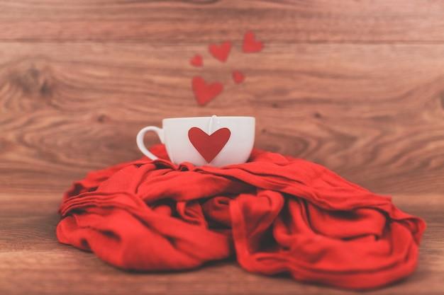 Tazza di caffè con un cuore rosso su una sciarpa