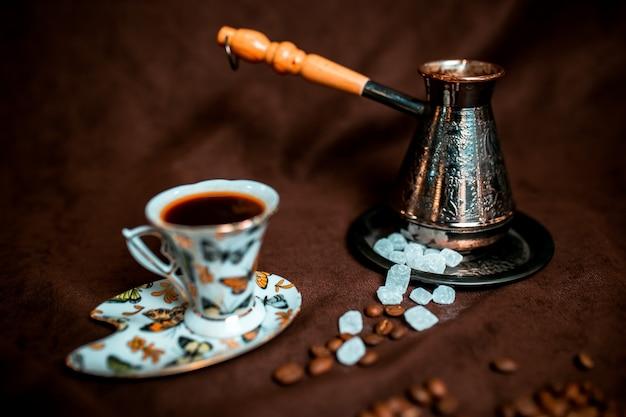Tazza di caffè con zollette di zucchero e chicchi di caffè intorno. cezve d'argento.