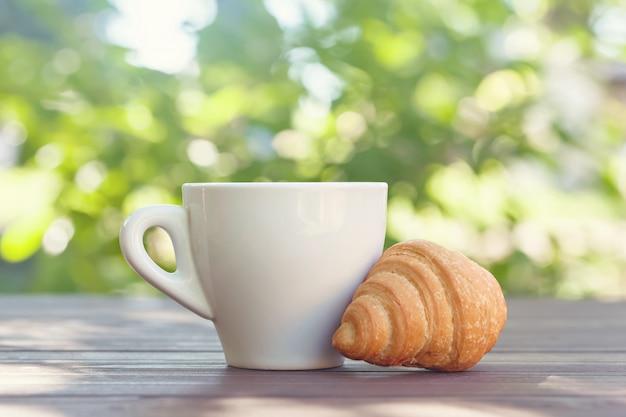Tazza di caffè, cornetto e fiori sul tavolo di legno