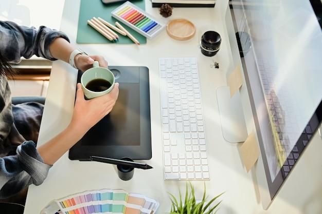 Tazza di caffè creativa della tenuta del progettista sul posto di lavoro dello studio dello scrittorio