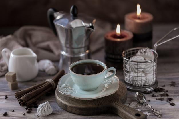Tazza di caffè crema con biscotti al cioccolato, marshmallow e candele accese.