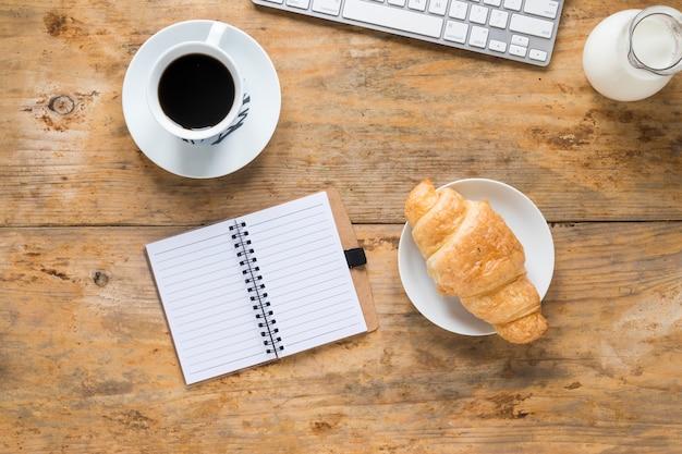 Tazza di caffè; croissant al forno; latte con tastiera e blocco note a spirale in bianco sulla scrivania in legno