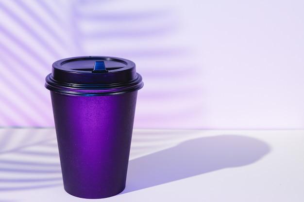 Tazza di caffè da asporto con ombre di fogliame, copia spazio