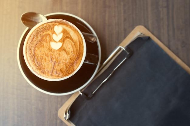 Tazza di caffè dall'alto, piatto laici immagine, con la nota di carta sul tavolo di legno.