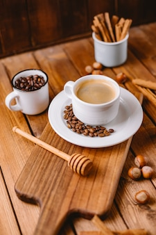 Tazza di caffè decorata con chicchi di caffè disposti sul verticale di bordo di servizio in legno