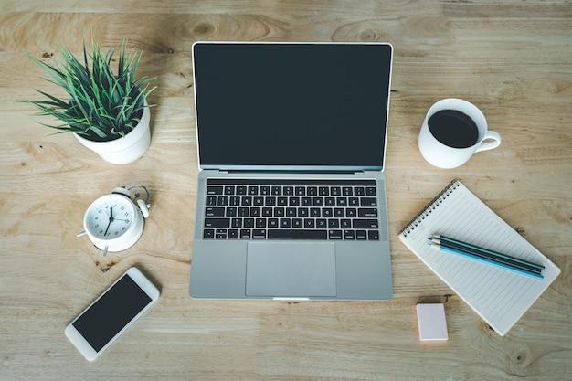Tazza di caffè del computer portatile e vaso dell'albero sulla tavola di legno. vista dall'alto scrivania tavolo