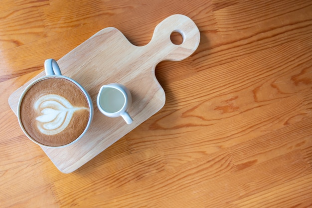 Tazza di caffè del latte con arte del latte sulla tavola di legno in caffetteria.