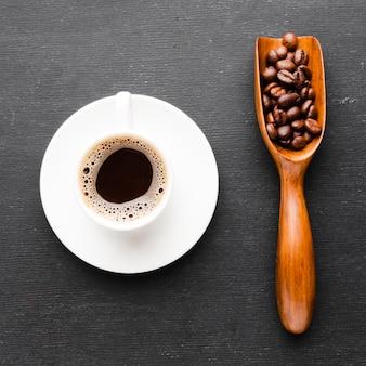 Tazza di caffè del primo piano con la paletta dei fagioli