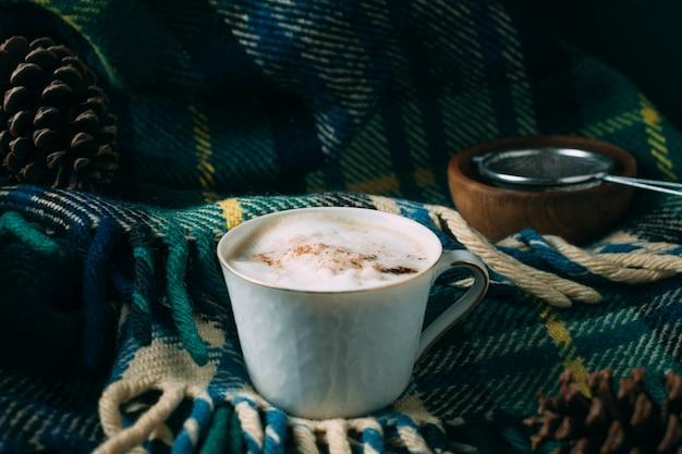 Tazza di caffè del primo piano con una coperta