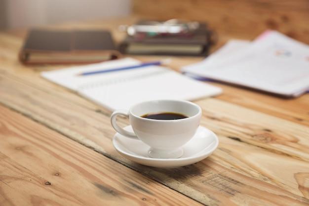 Tazza di caffè del primo piano sulla scrivania con carta e grafico di analisi.