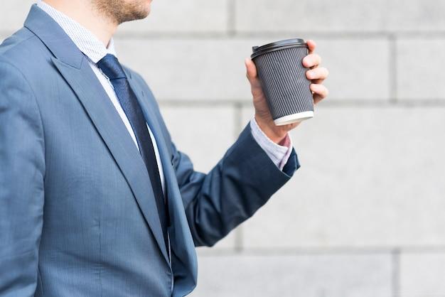 Tazza di caffè della holding dell'uomo d'affari