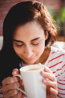 Tazza di caffè della holding della bella donna