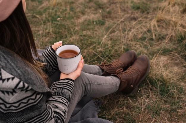 Tazza di caffè della holding della donna del primo piano