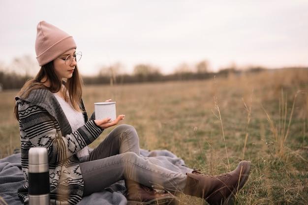 Tazza di caffè della holding della donna della foto a figura intera
