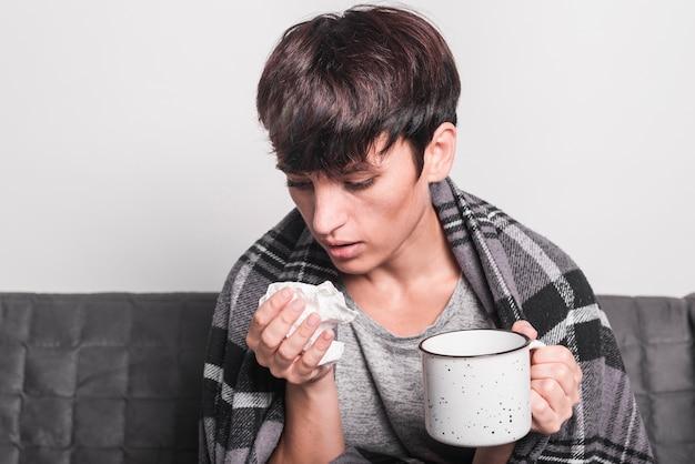 Tazza di caffè della holding della donna malata che starnutisce in carta velina