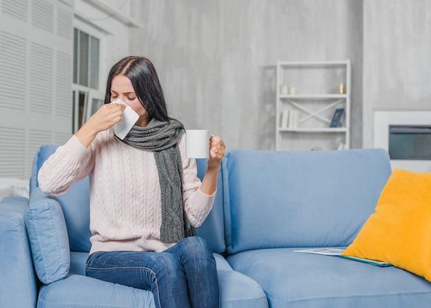Tazza di caffè della holding della giovane donna che soffre dalla tosse